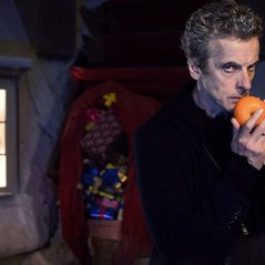 The Doctor gently cradling a tangerine